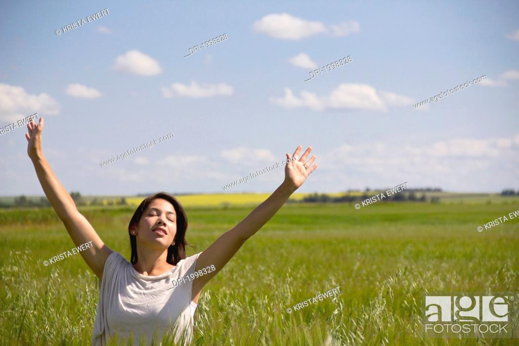 Stock Photo: woman in a field with raised hands, three hills alberta canada.