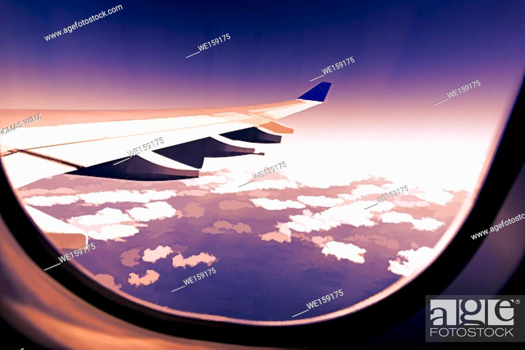Stock Photo: Looking out airplane window over puffy clouds , USA.