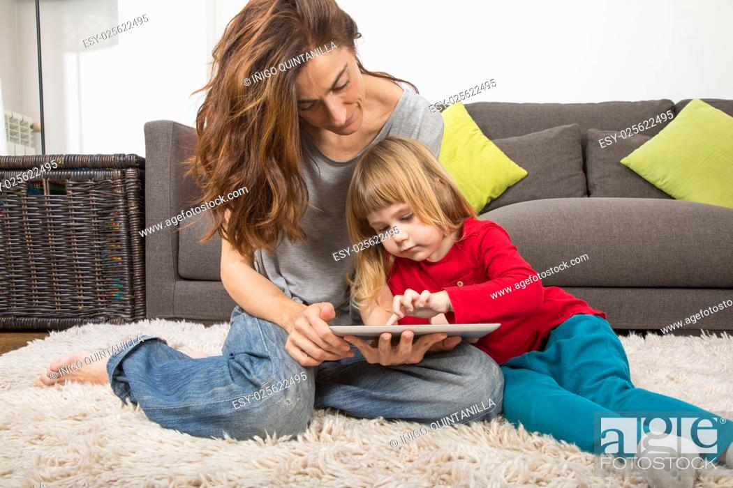 Stock Photo: blonde three years old child and mother, with red, green and grey clothes, touching and watching digital tablet to surf internet, sitting on carpet indoor home.