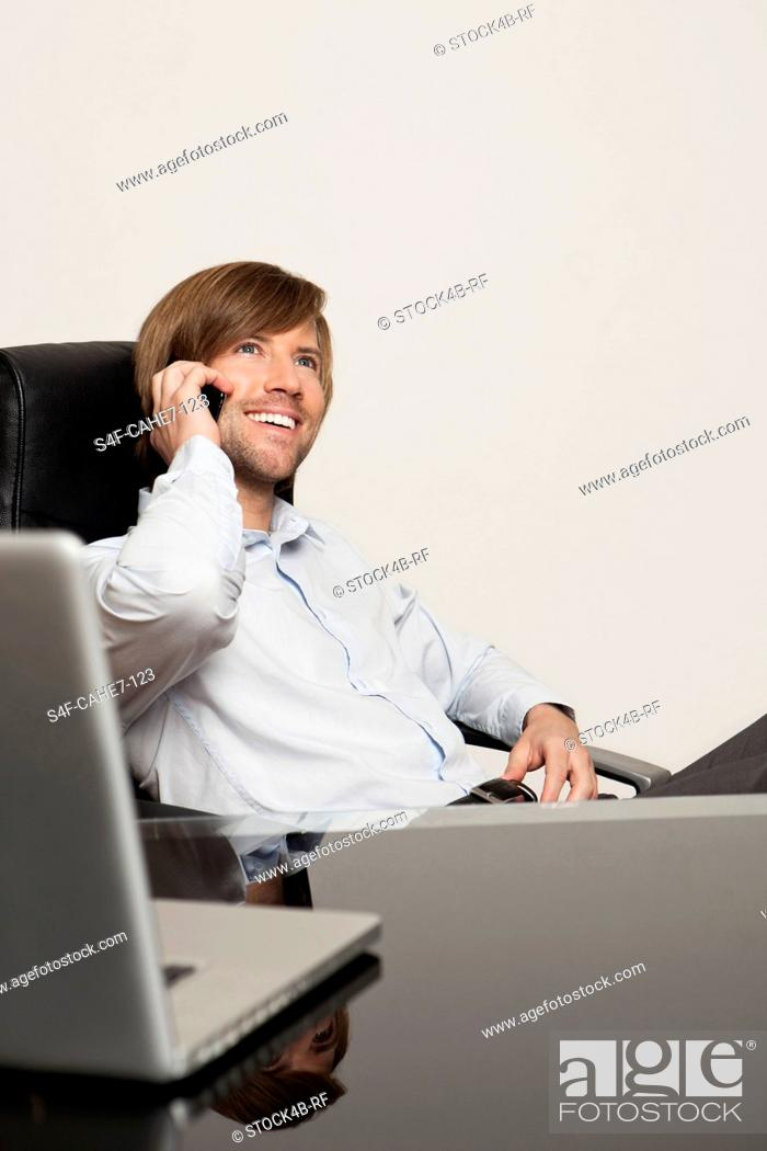 Stock Photo: Happy businessman at desk on the phone.