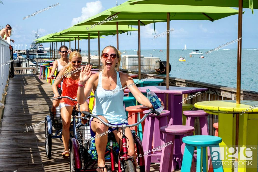 Stock Photo: Florida, Key West, Sunset Key, Gulf of Mexico, Sunset Pier, restaurant, bar, pub, tables, umbrellas, colorful, woman, rental, bicycle, tricycle, friends.
