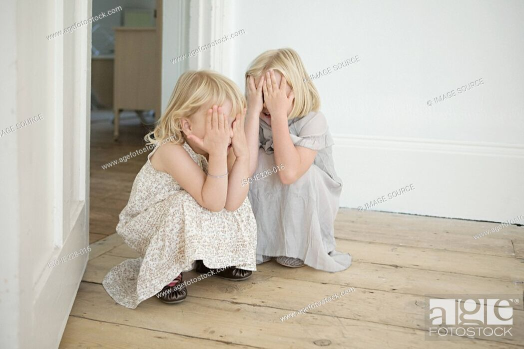 Stock Photo: Sisters playing hide and seek.