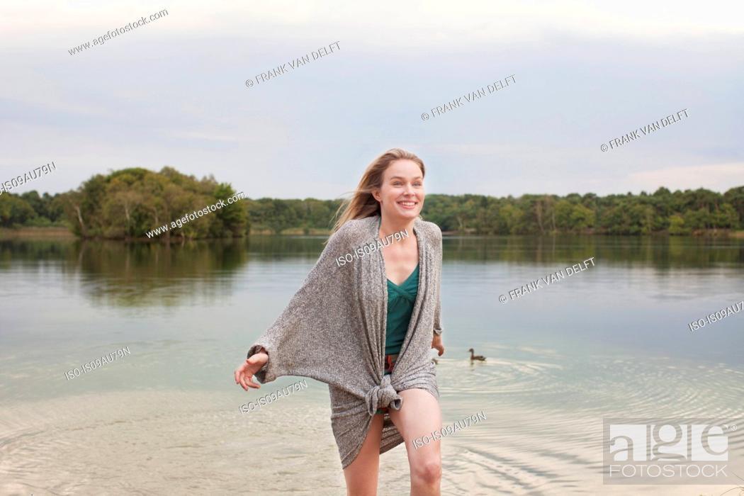 Photo de stock: Young woman playing in lake.