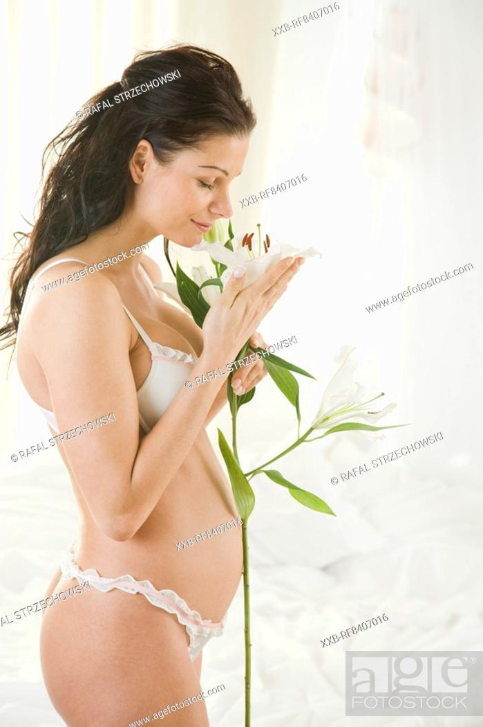 Stock Photo: pregaant woman with lilies.