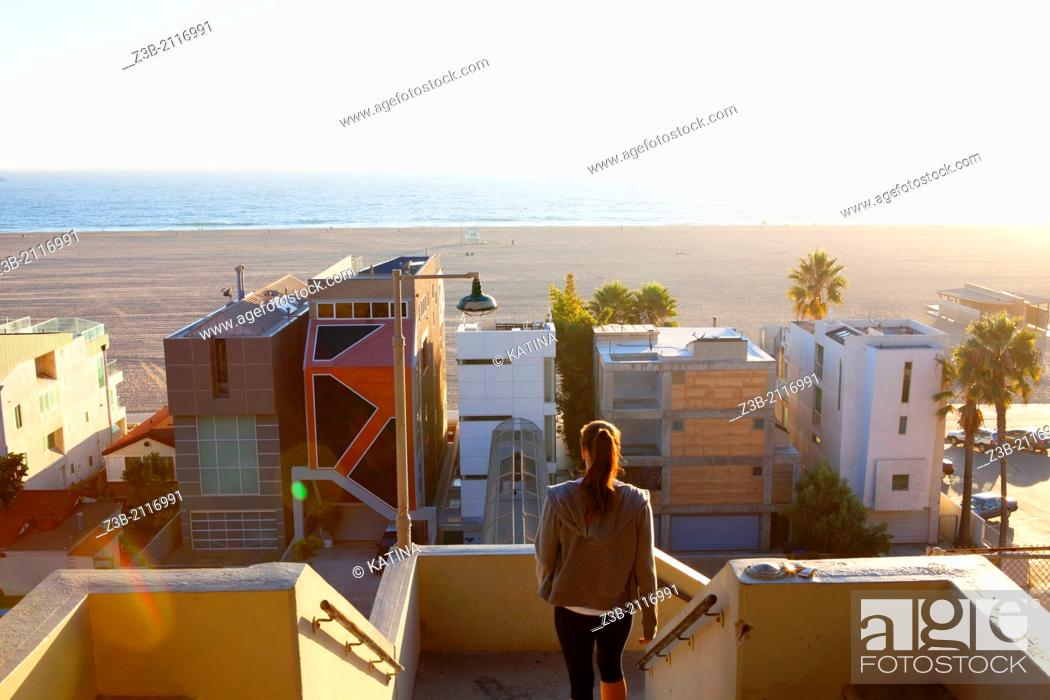 Stock Photo: One woman leaves Palisades Park on sunny afternoon, with modern architecture beachfront homes and Pacific Ocean in distance, Santa Monica, City of Los Angeles.