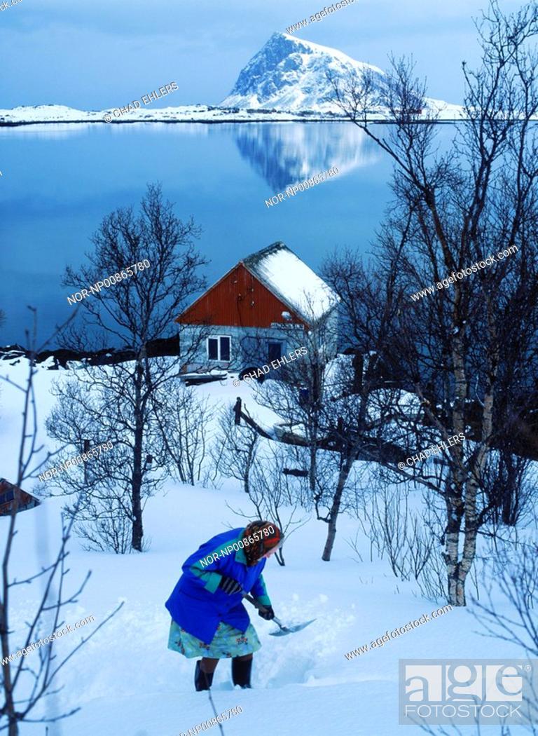 Stock Photo: Elderly woman shoveling snow at home in Lofoten Islands, Norway.