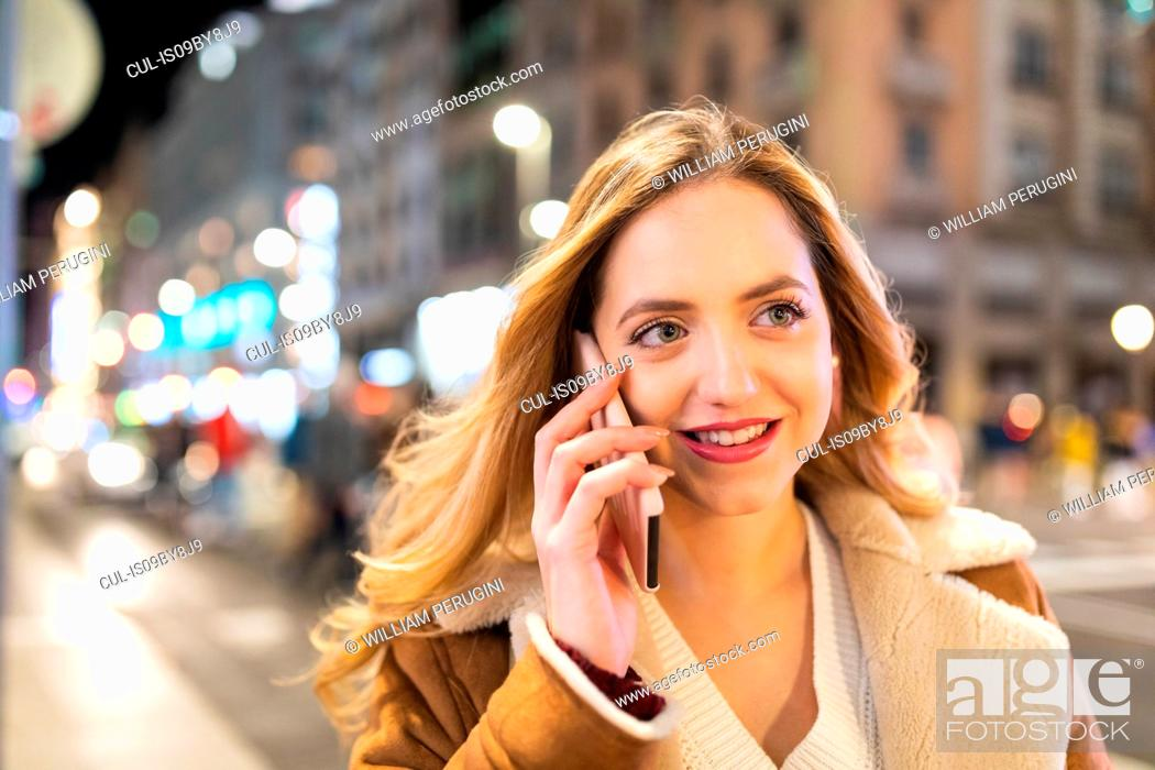 Stock Photo: Young woman with long blond hair making smartphone call on sidewalk at night, Madrid, Spain.