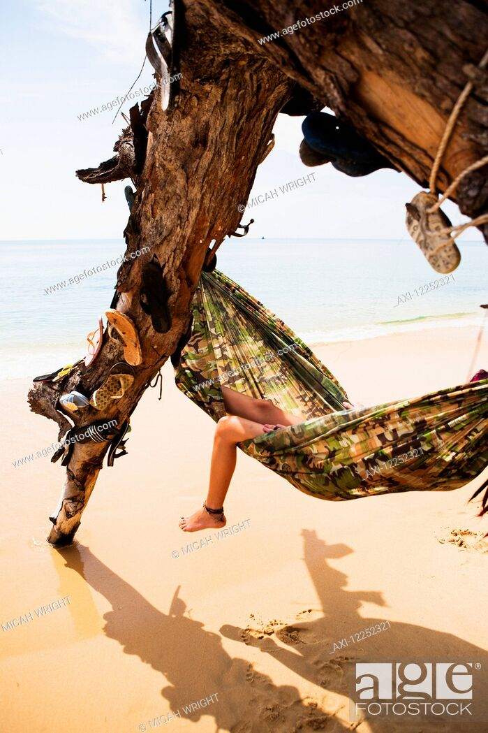 Imagen: Resting in a hammock in a tree decorated with lost flip flops; Sihanoukville, Cambodia.