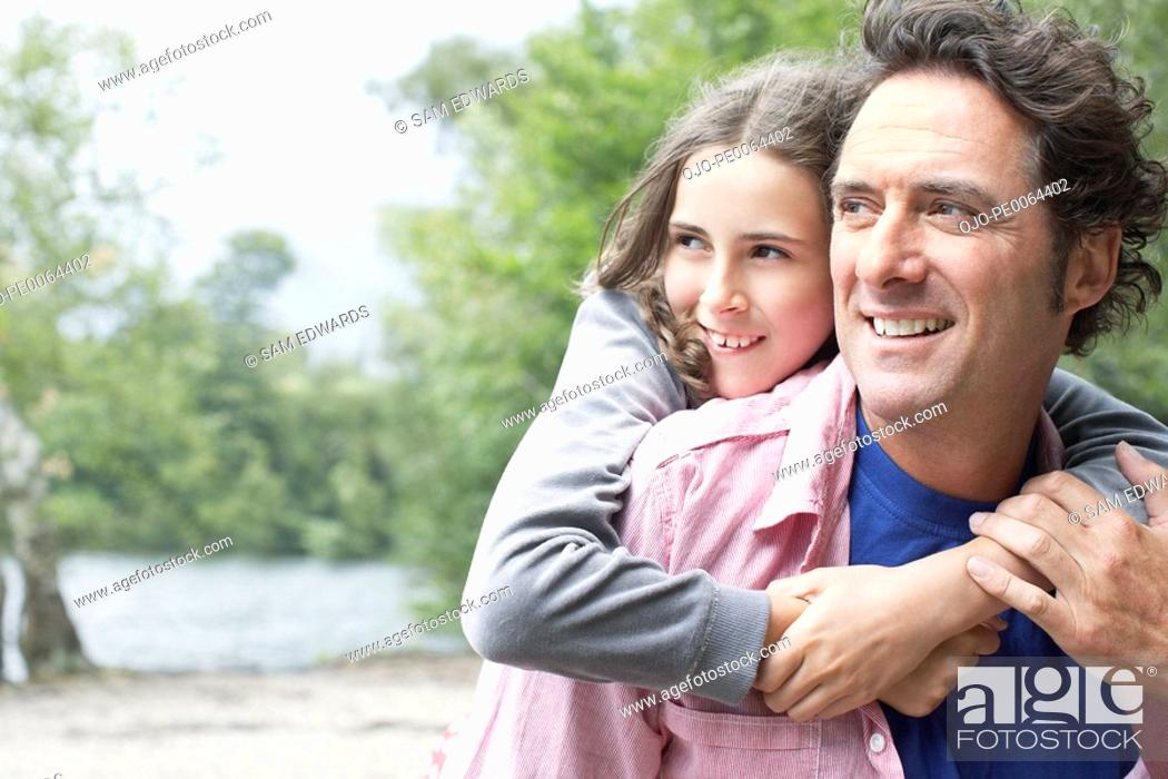 Stock Photo: Daughter hugging father outdoors.