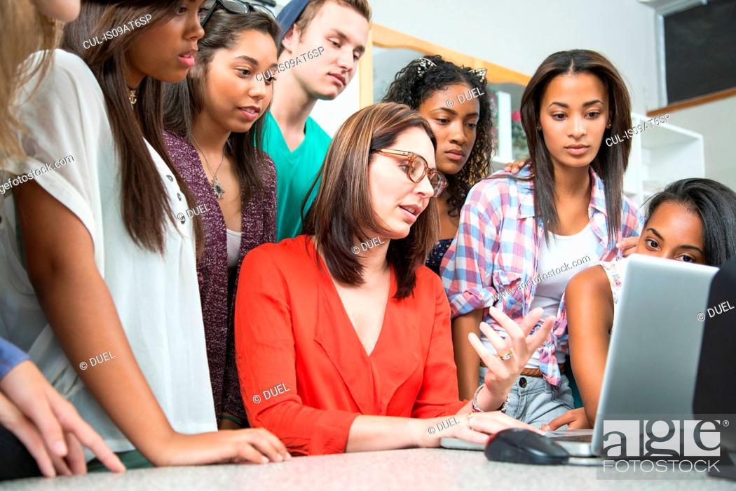 Stock Photo: Mid adult female teacher explaining on laptop to high school students.