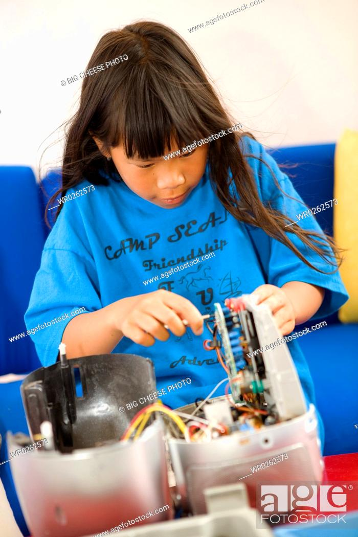 Stock Photo: Close-up of a girl repairing radio.