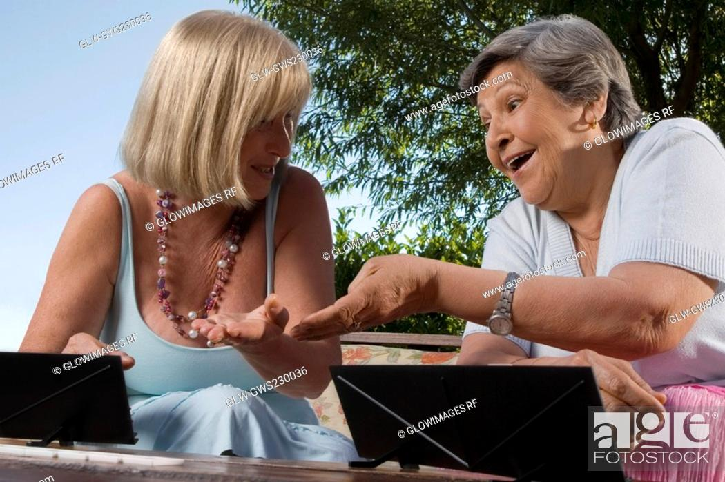 Stock Photo: Two senior women playing games and smiling.