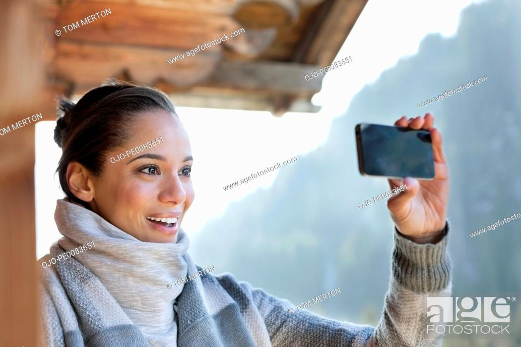Stock Photo: Smiling woman taking photograph with camera phone.