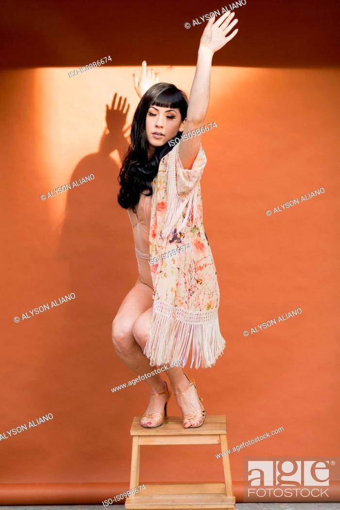 Photo de stock: Young woman in tasseled negligee poised while dancing on stool.