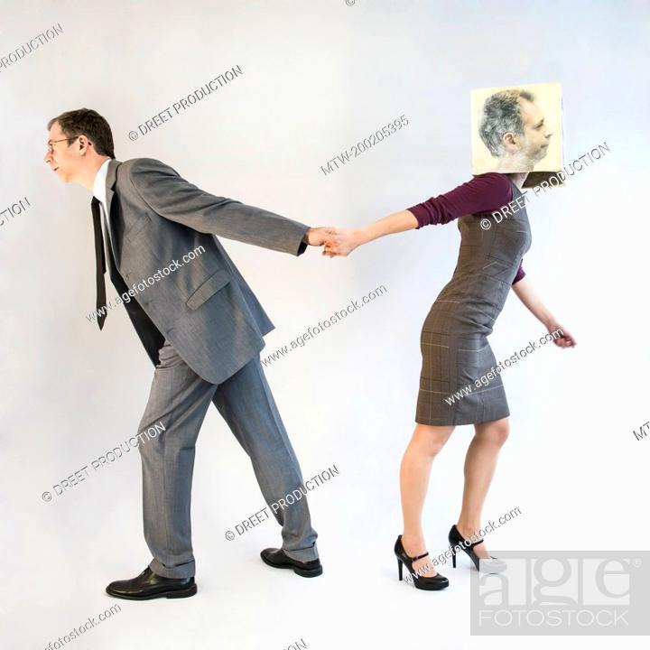 Stock Photo: Businessman pulling businesswoman wearing mask.