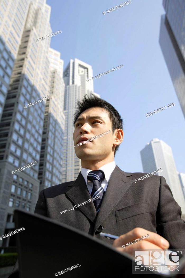 Stock Photo: Businessman with office buildings, portrait.