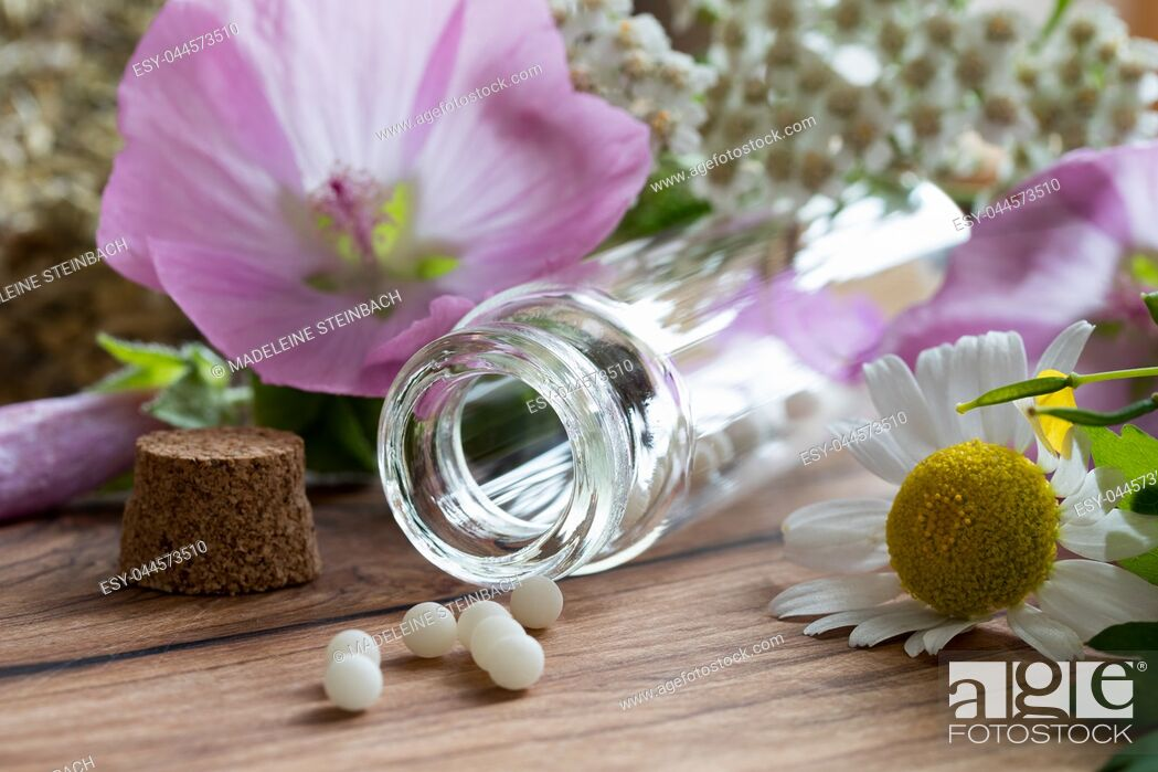 Stock Photo: A bottle of homeopathic globules with chamomile, yarrow and other herbs and flowers in the background.