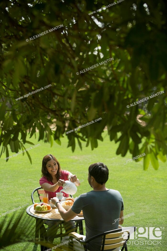 Stock Photo: woman pouring coffee for man in garden.