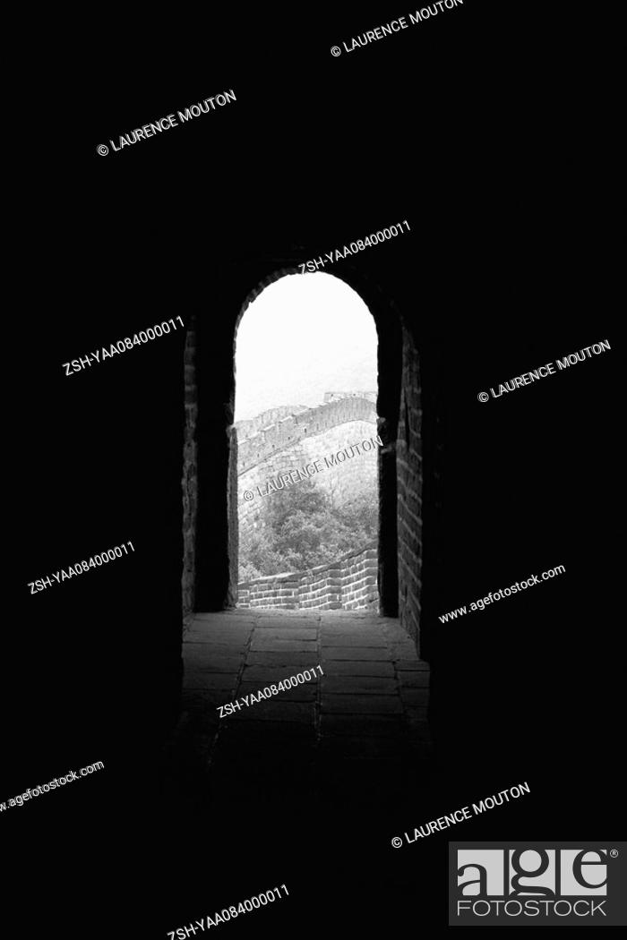 Stock Photo: Looking down dark passageway to open arched doorway of room perched atop Great Wall of China.