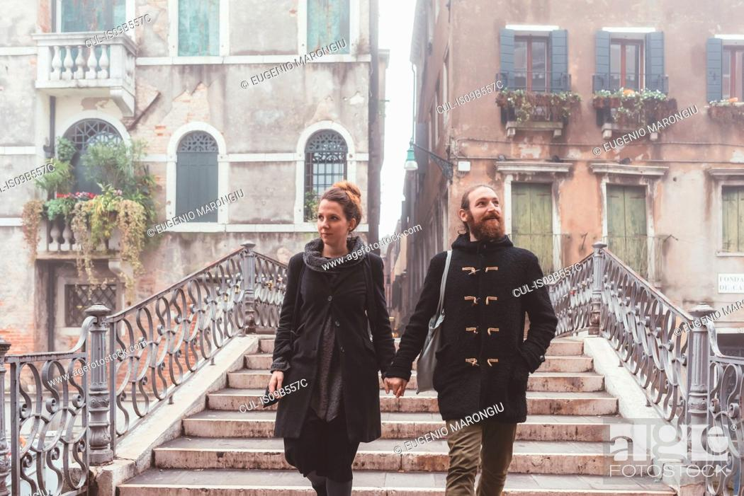 Imagen: Couple holding hands and moving down stairway, Venice, Italy.