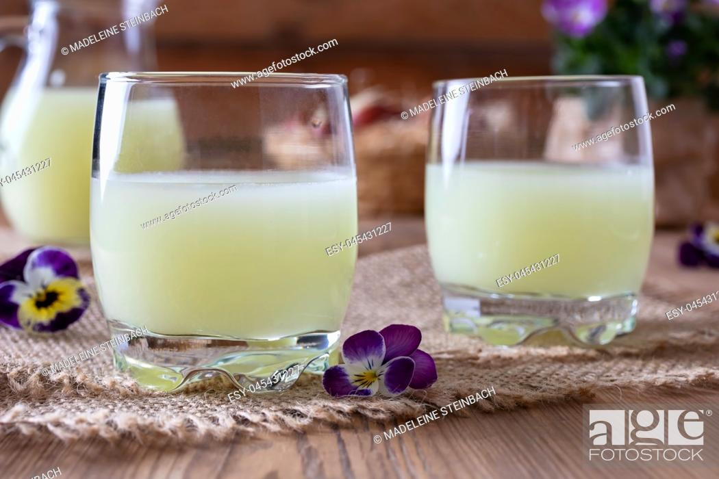 Stock Photo: Two glasses of fresh whey with pansy flowers.