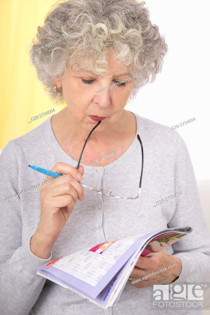 Stock Photo: Senior woman sitting on her sofa, thoughtful and peacefully making crosswords, her spectacles in her mouth.
