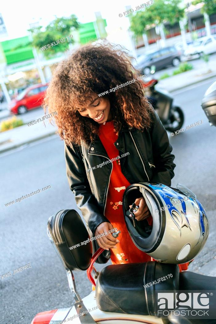 Stock Photo: Smiling young woman removing safety lock from her motorcycle.