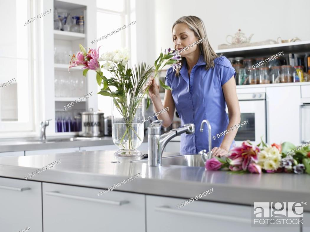 Stock Photo: Mid adult woman in kitchen smelling flowers in vase.
