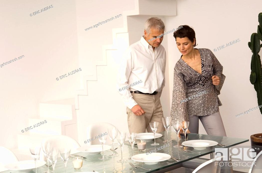 Stock Photo: Mid adult woman setting a dining table and a mature man standing beside her.