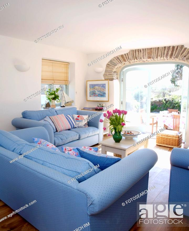 Stock Photo Blue Sofas In White Coastal Living Room With French Windows To Patio