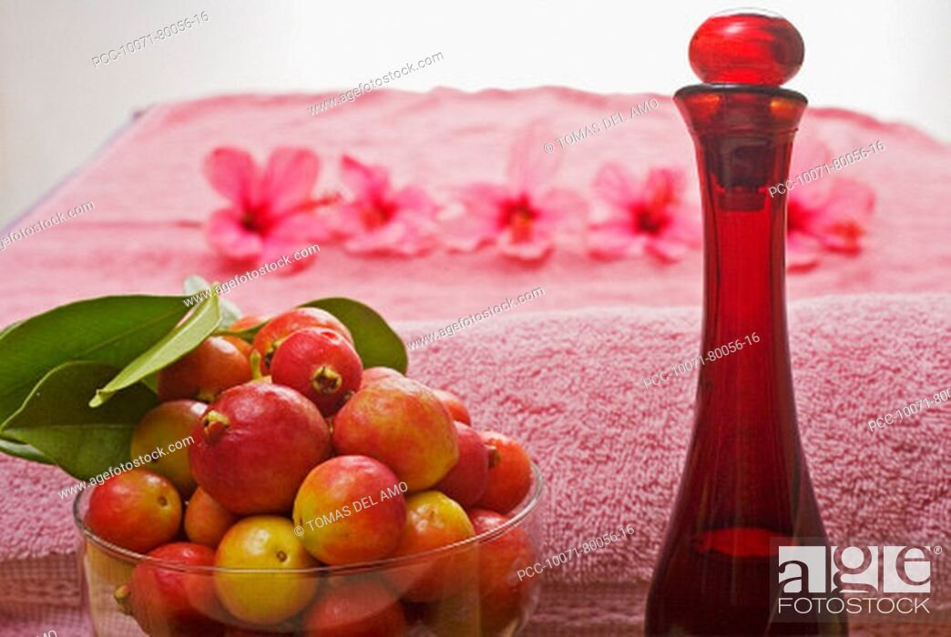 Stock Photo: Spa elements, a pink towel, bowl of fruit, glass bottle and line of flowers blurred in background.