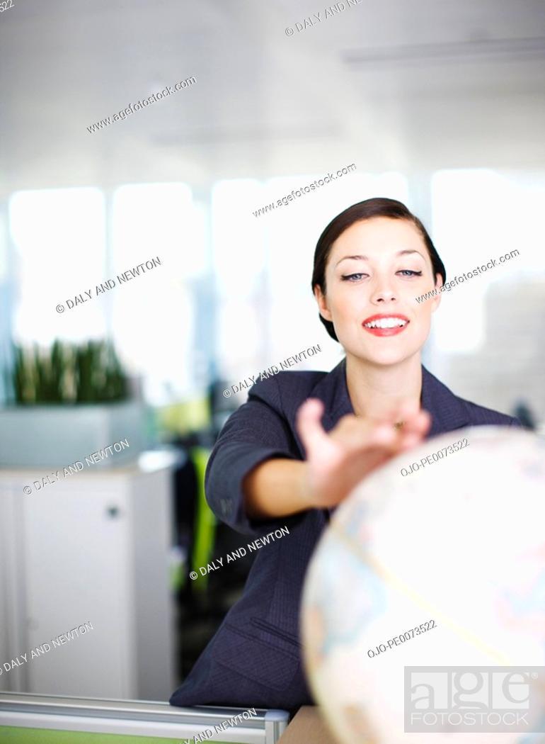 Stock Photo: Smiling businesswoman reaching for globe.