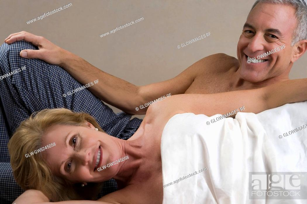 Stock Photo: Portrait of a mature woman lying down with a senior man smiling behind her.
