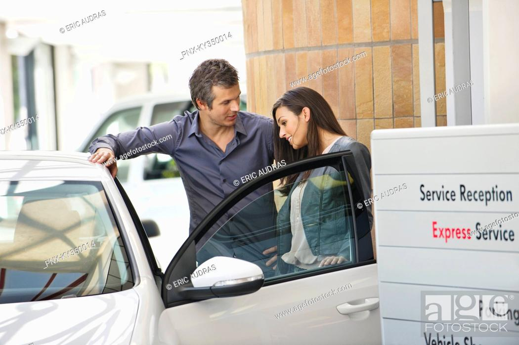 Stock Photo: Couple looking inside car at showroom.