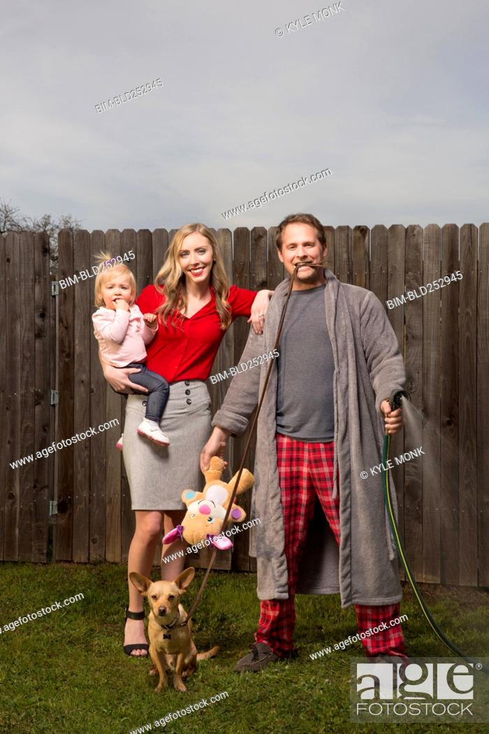 Stock Photo: Caucasian couple posing near wooden fence with baby daughter.