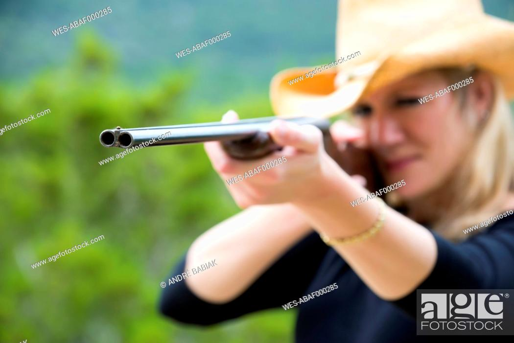 Stock Photo: USA, Texas, Mid adult woman aiming rifle.