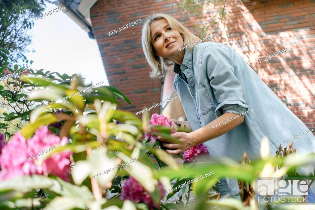 Stock Photo: Smiling mature woman with flowers in garden.