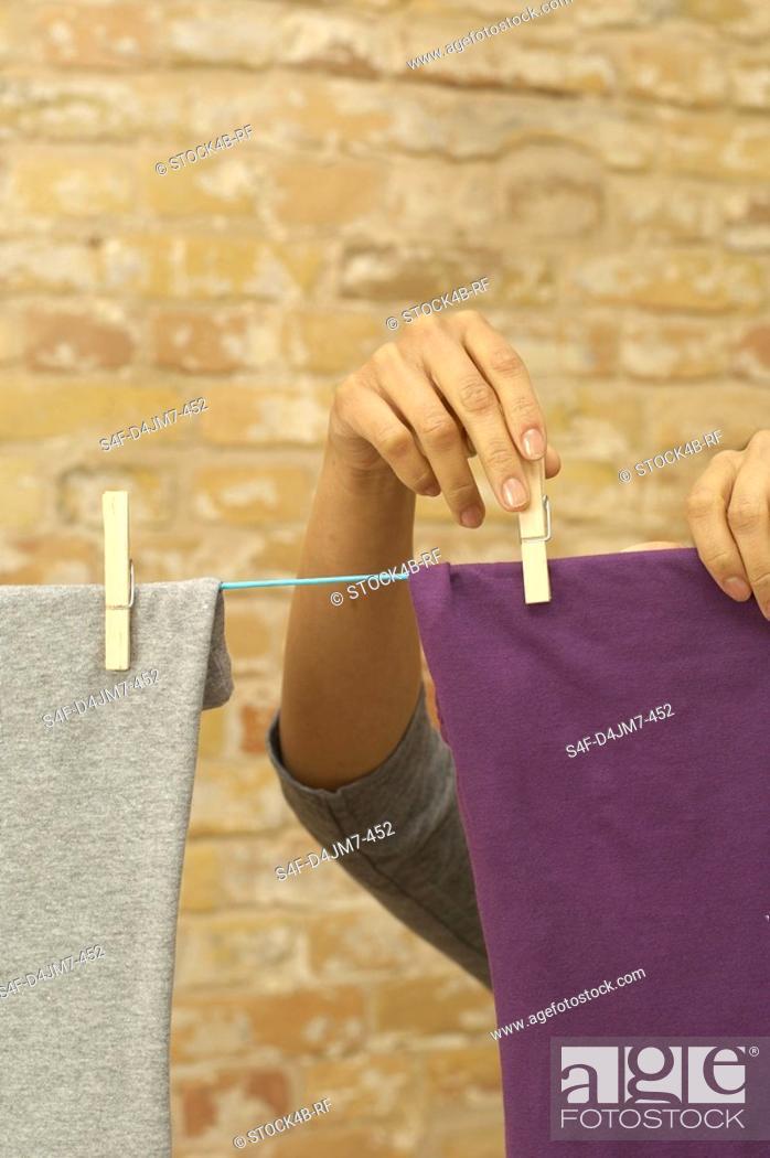 Stock Photo: Woman hanging washing on clothesline.