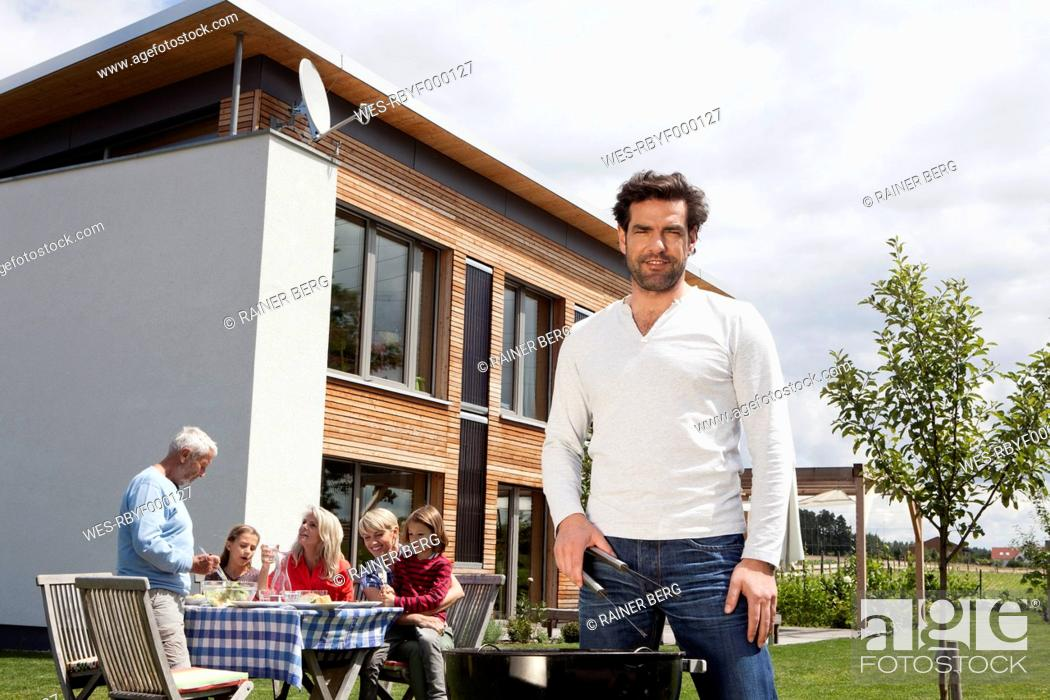 Stock Photo: Germany, Bavaria, Nuremberg, Man cooking barbecue, family sitting in garden.