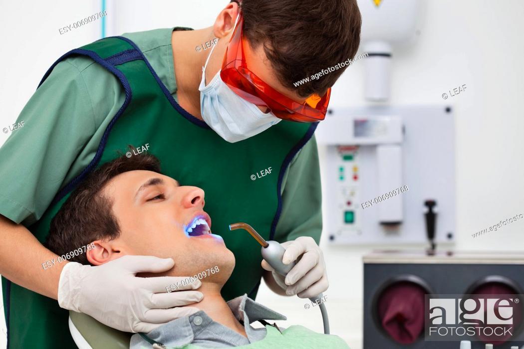Stock Photo: Dentist using UV light on patients teeth.