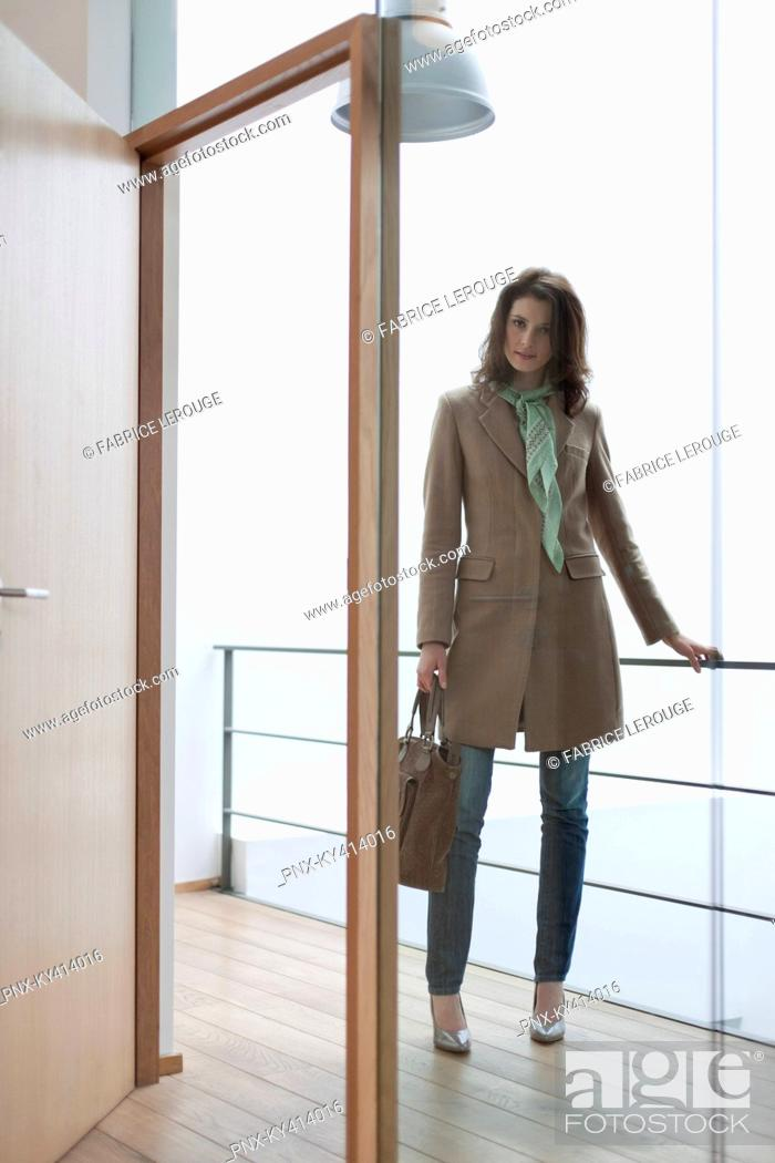Stock Photo: Woman standing at the doorway.