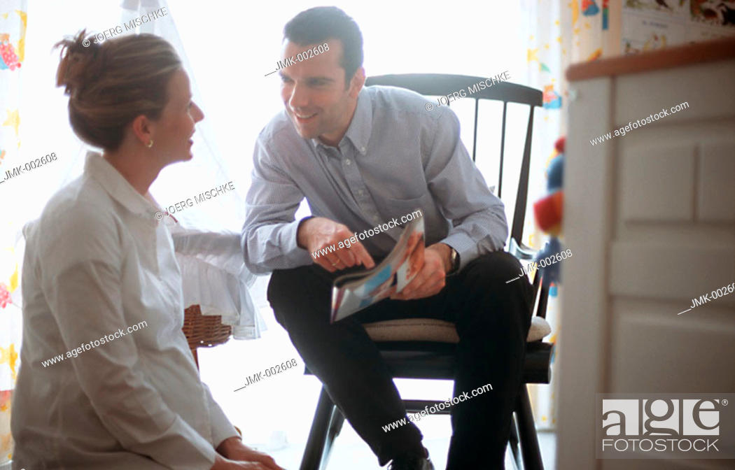 Stock Photo: A young couple, young man and young pregnant woman, 25-30 30-35 35-40 years old, sitting in the nursery, talking.