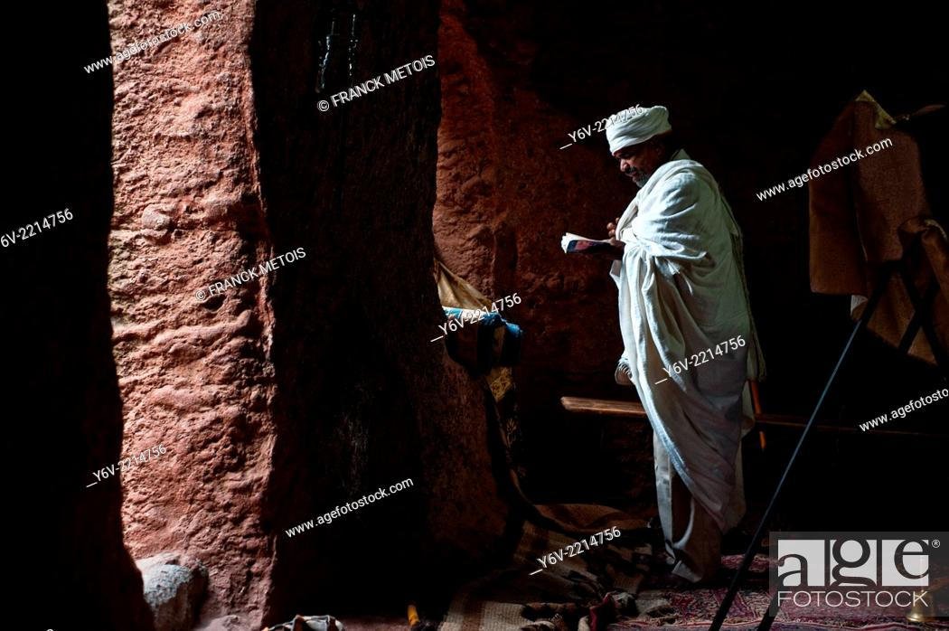 Stock Photo: Priest reading the Bible during a mass in a orthodox church i.e. Bet Giyorgis church. Lalibela, Ethiopia.