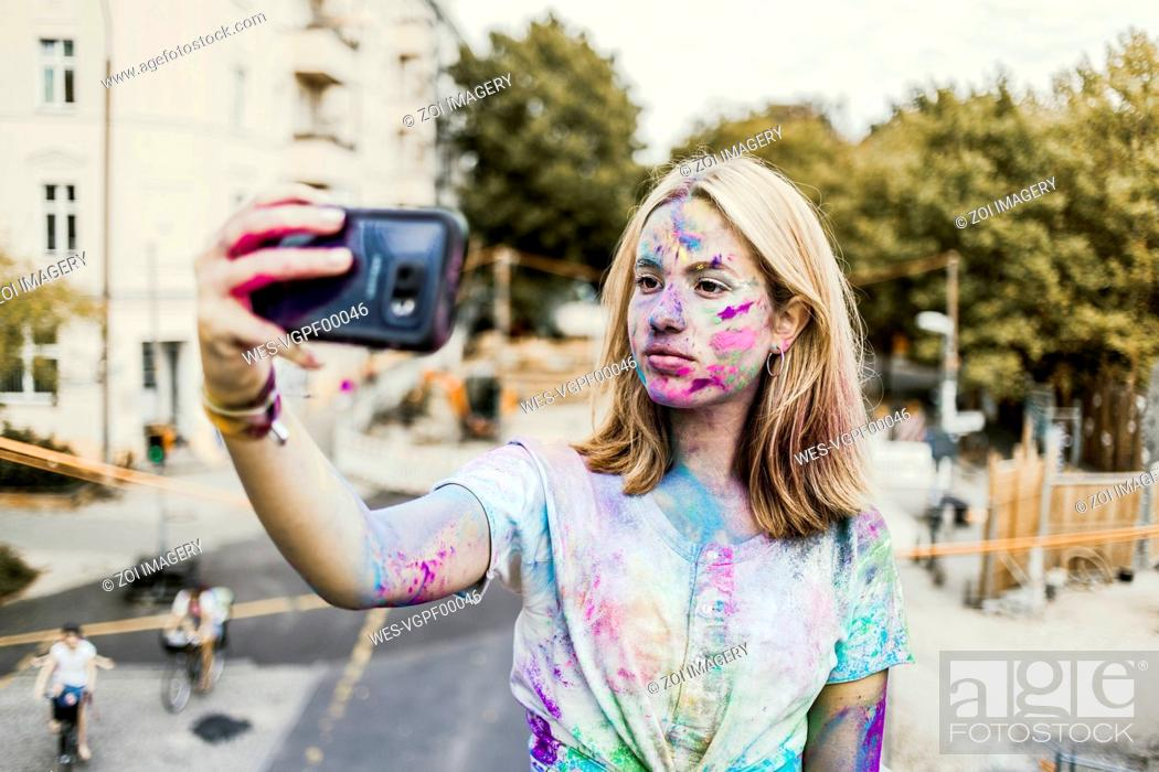 Stock Photo: Gir Holi powder colours in her face, taking selfie, Germany.
