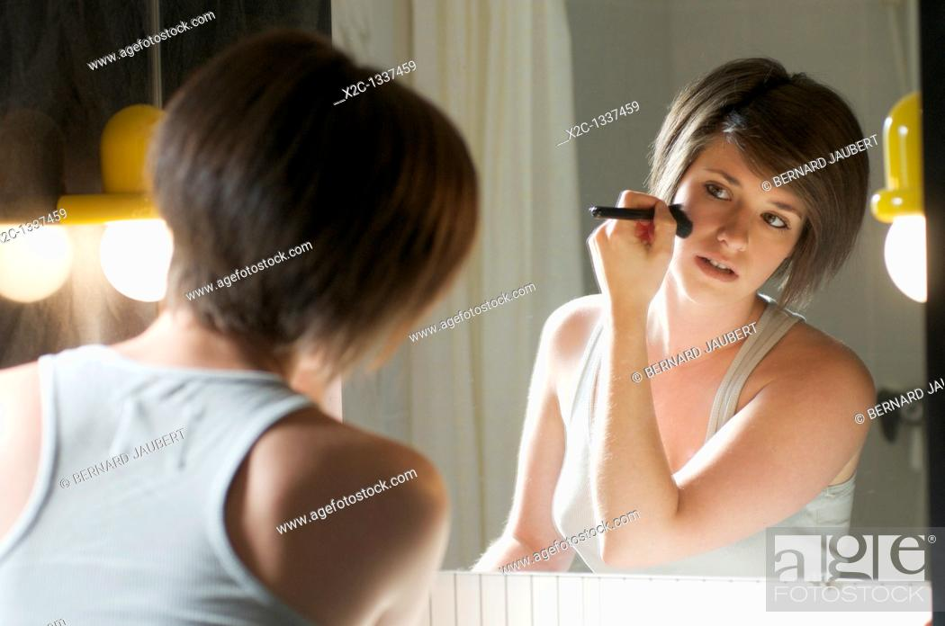 Stock Photo: Young woman applying blush in front of mirror.