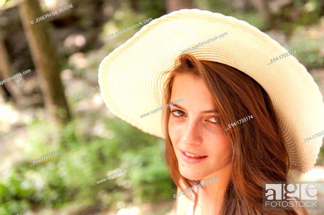 Stock Photo: A happy 20 year old brunette woman wearing a white top and a floppy straw hat in a forest setting looking directly at the camera.