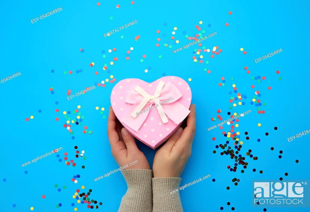 Stock Photo: female hand holding a pink cardboard box with a bow on a blue background with multi-colored confetti, concept of giving a gift for a holiday.