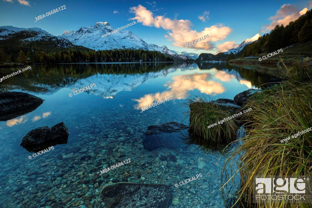 Stock Photo: Dawn illuminates the peaks reflected in the calm waters of Lake Sils Engadine Canton of Graubünden Switzerland Europe.