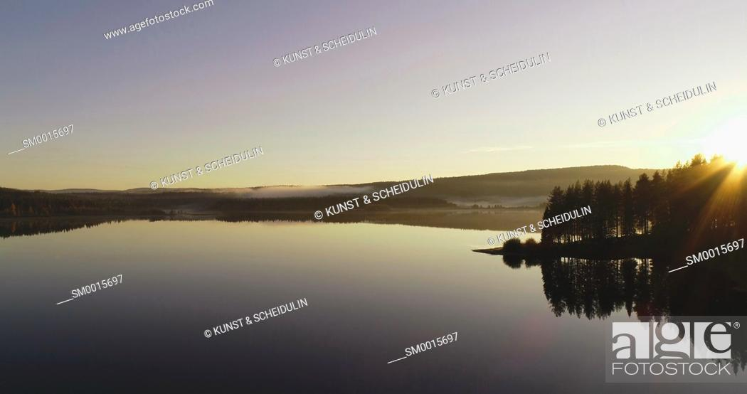 Stock Photo: The sun is rising over a glassy lake in northern Sweden - aerial shot.