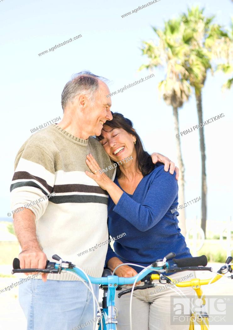 Stock Photo: Couple walking bicycles on beach.